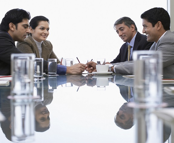 A group of four businesspeople talking at a table